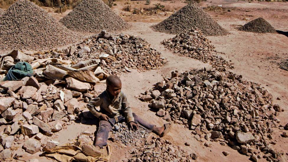 Niño golpeando una roca para extraerl cobalto en la República Democrática del Congo