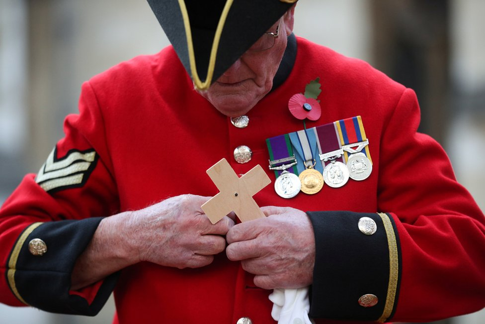 A Chelsea Pensioner holds a cross in the Field of Remembrance at Westminster Abbey in London
