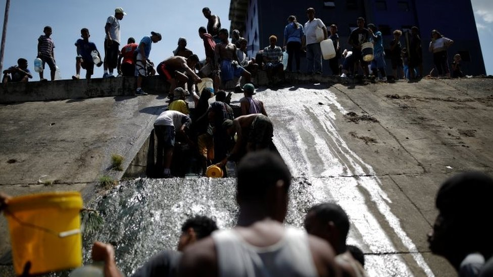 People collect water released through a sewage drain that feeds into the Guaire River, which carries most of the city's wastewater, in Caracas, Venezuela March 11, 2019.