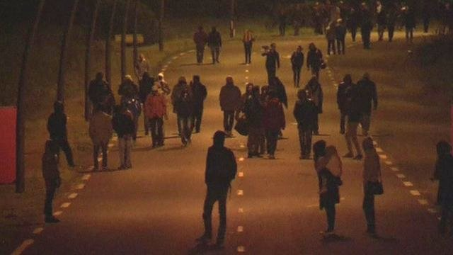 Migrants walk towards Channel tunnel at night