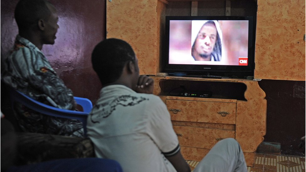 Somali men in Mogadishu in September 2014 watch a TV news bulletin on the killing of Al-Shabab leader Ahmed Abdi Godane.