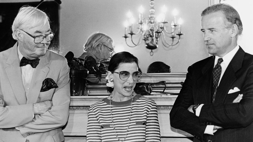 Supreme Court nominee Ruth Bader Ginsburg answering reporter's questions during courtesy call to Senator Joe Biden's office. She's standing with Sens. Biden and Daniel Patrick Moynihan 15 June, 1993