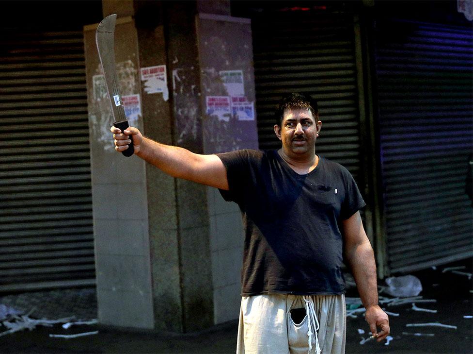 El dueño de una tienda sostiene un machete después de permanecer despierto toda la noche para proteger su negocio durante los saqueos y protestas generalizados en Durban, Sudáfrica, el 12 de julio de 2021.