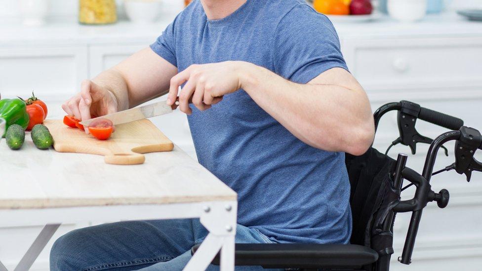 Un hombre en silla de ruedas cortando comida