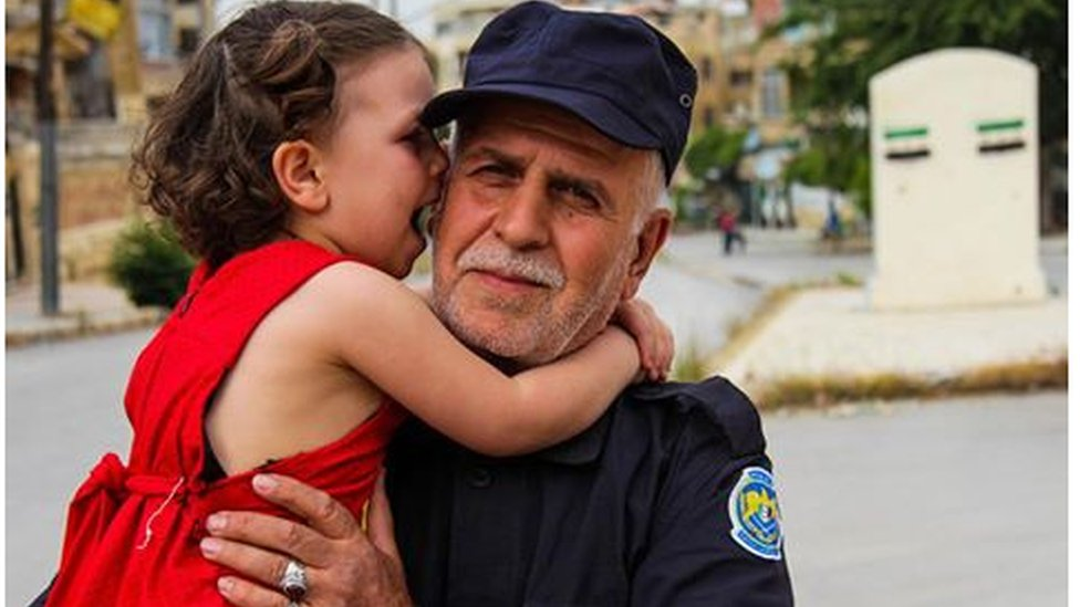 Free Syrian Police officer holds a little girl in a red dress