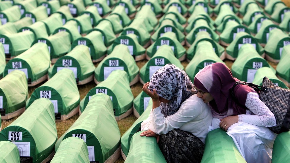 Foto de archivo: familiares lloran a frente los ataúdes de víctimas del genocidio