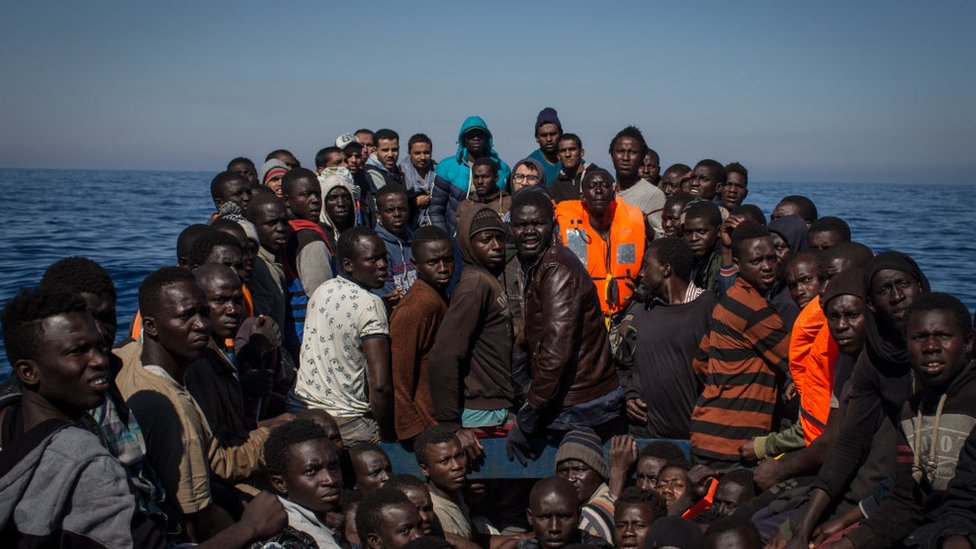 Migrants afloat in the Mediterranean wait to be rescued by Italian authorities.