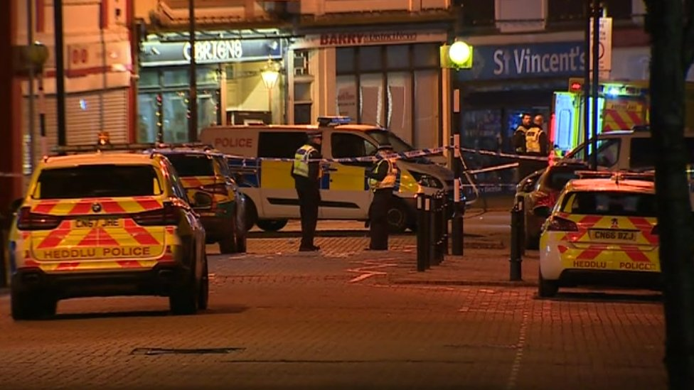 Police cars parked near cordoned off area