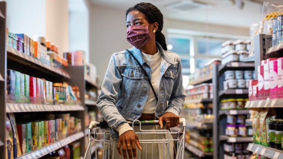 A black young woman pushing a trolley at a supermarket