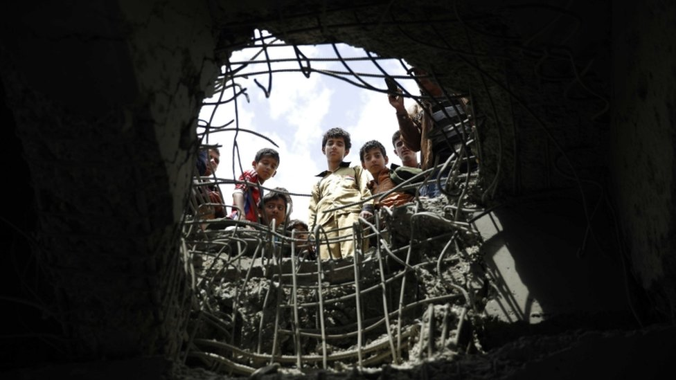 Boys look through a hole made by a Saudi-led airstrike on a bridge in Sana'a, Yemen, 23 March 2016
