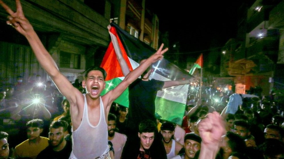 Palestinians celebrate in the streets following a ceasefire, in the southern Gaza Strip