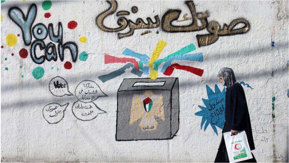 Una mujer camina frente a un mural con publicidad electoral en la Ciudad de Gaza, abril 2021