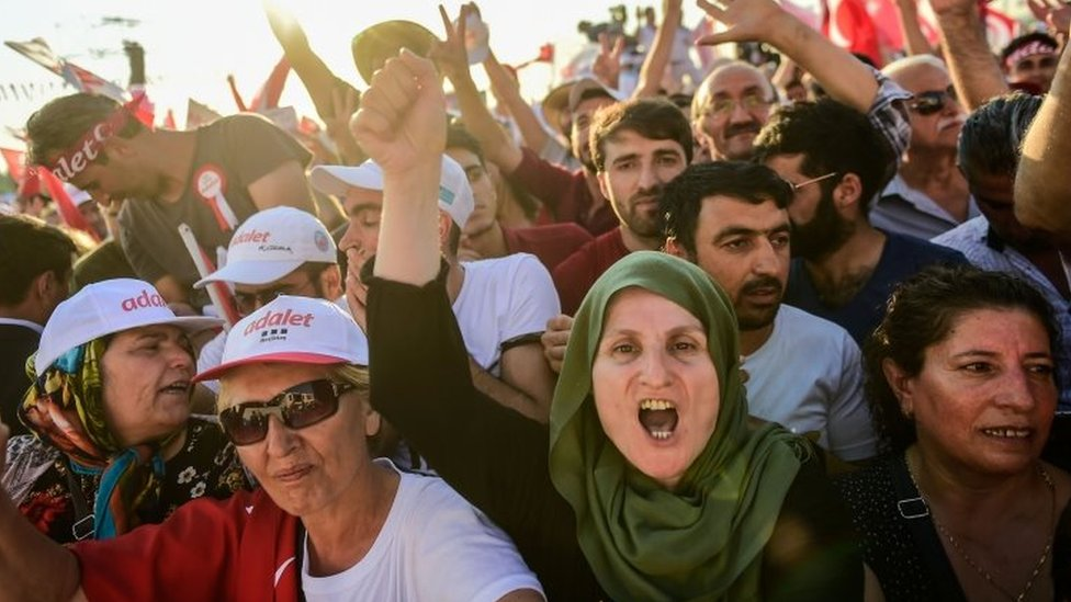 People cheer as Turkey's main opposition CHP leader Kemal Kilicdaroglu throws flowers to supporters during a rally in Istanbul (09 July 2017)