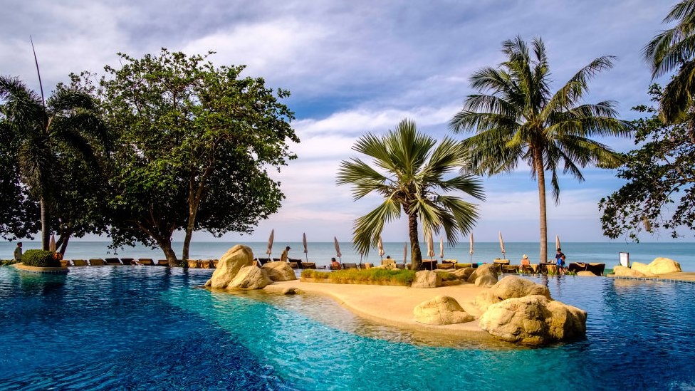 The pool of a tourist resort, surrounded by palm trees, at White Sand Beach on Koh Chang.