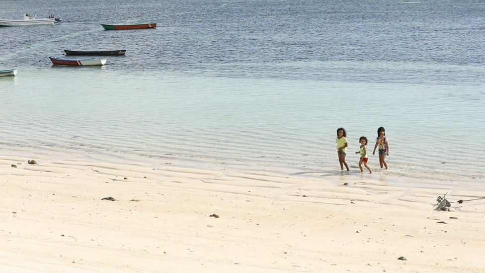 Children play on a beach in Rote