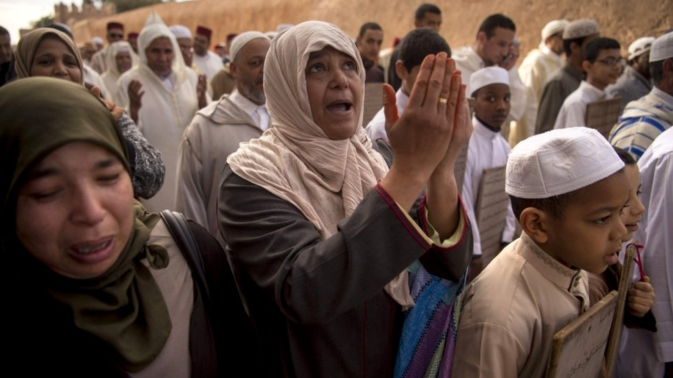 A woman looks to the sky while in a crowd praying