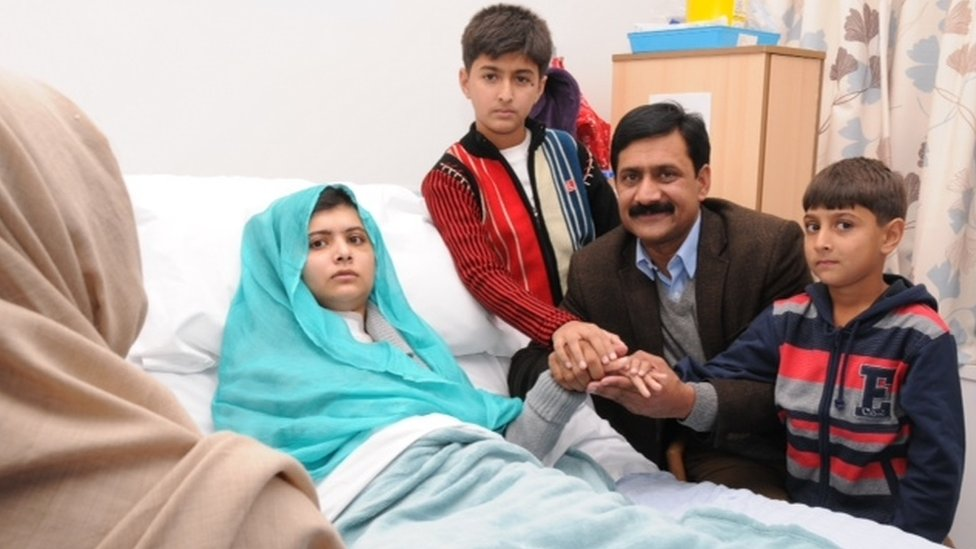 Malala in hospital bed surrounded by her family