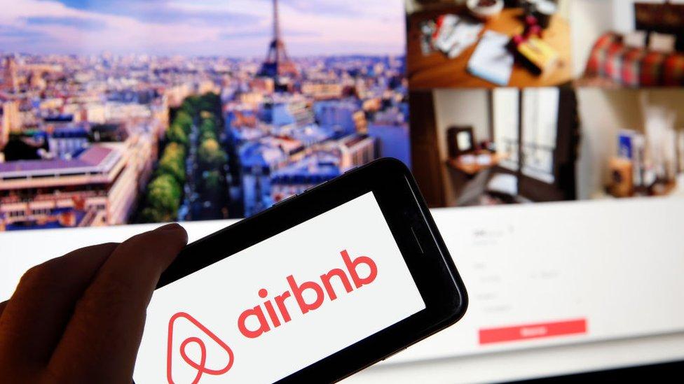 Logo de Airbnb con la página web de fondo.