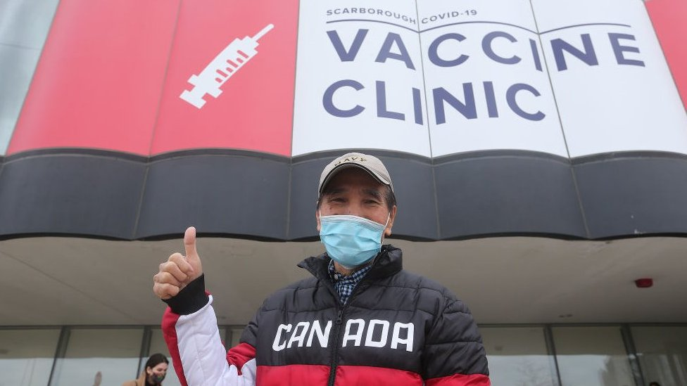 A man in a Canada jacket showing thumbs up at a vaccine centre