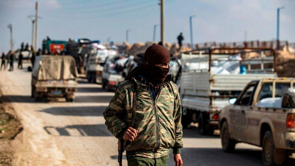 """أحد عناصر دورية الأمن الداخلي يقف أمام قافلة شاحنات في مخيم الهول الذي تديره القوات الكردية، ينقل نساء وأطفال سوريين يشتبه في ارتباطهم بمقاتلي تنظيم """"الدولة الإسلامية""""."""