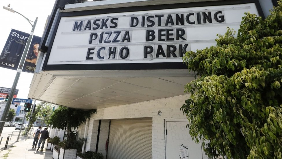 """A sign reading """"Masks Distancing Pizza Beer"""" is displayed above a restaurant and bar on Sunset Boulevard amid the COVID-19 pandemic on June 29, 2020 in Los Angeles"""