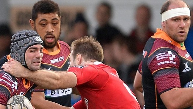 Adam Hughes of Newport Gwent Dragons is tackled by Tomas O'Leary