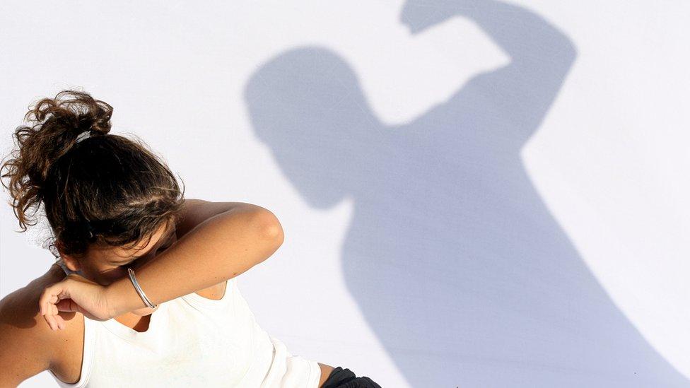 Mujer amenazada por la sombra de un hombre con el puño en alto.