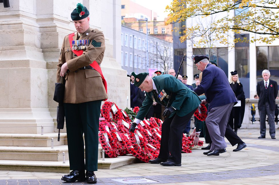 Men lay wreaths at the Cenotaph at Belfast City Hall