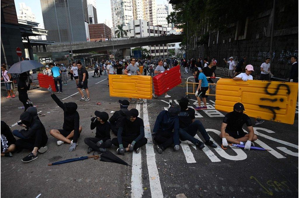 11月16日,有香港市民在街頭清除抗議人士擺放的障礙物。