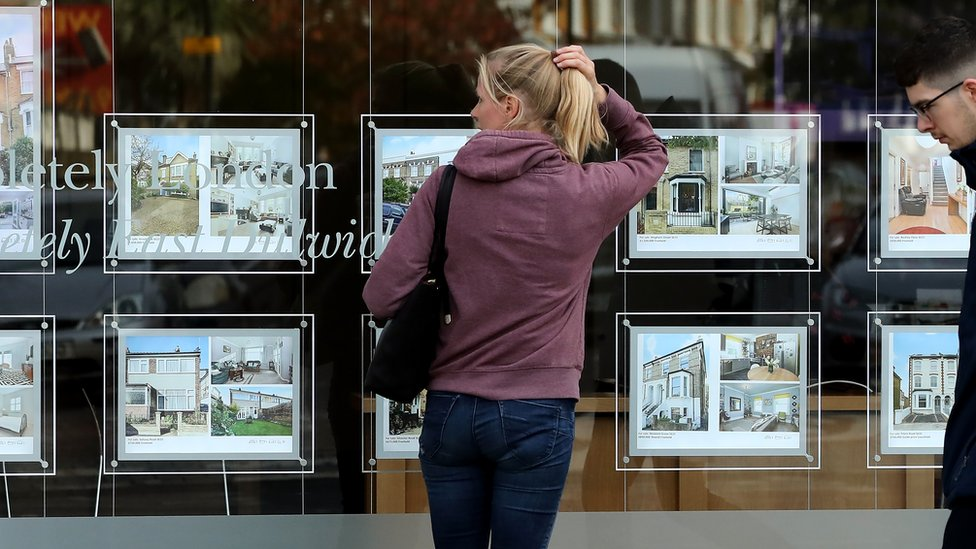 A woman looks in an estate agent's window in London, England.