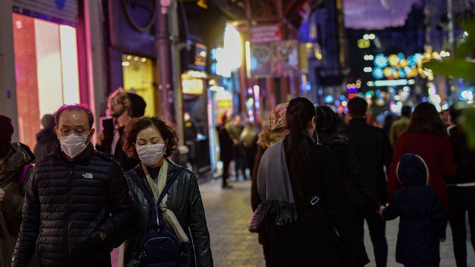 İstanbul, Beyoğlu'ndaki İstiklal Caddesi'nde maskeyle dolaşan turistler.