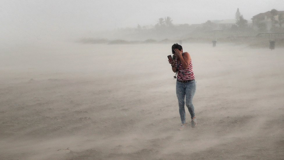 A woman seeks cover from wind, blowing sand and rain whipped up by Hurricane Dorian as she walks on the beach on September 2, 2019 in Cocoa Beach, Florida.