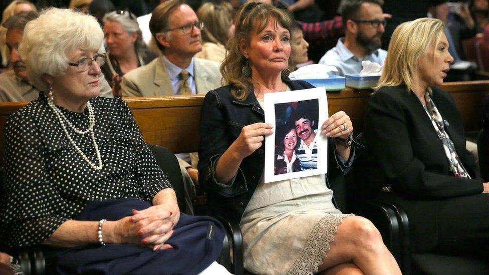 Una mujer sostiene una foto de Cheri Domingo y de su novio Gregory Sánchez, ambos asesinados en su casa en 1981.