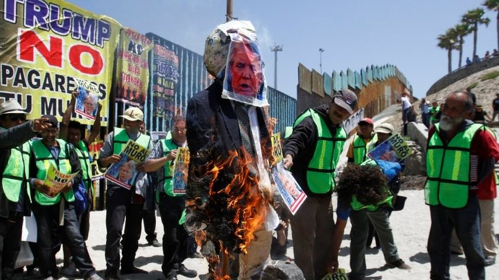 """Demonstrators burn an effigy depicting U.S. President Donald Trump during a protest against the immigration policies of Trump""""s government near the border fence between Mexico and the U.S., in Tijuana, Mexico May 10, 2018"""
