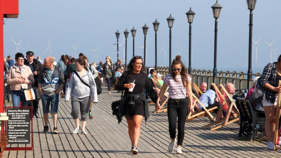 People walking along Skegness Pier