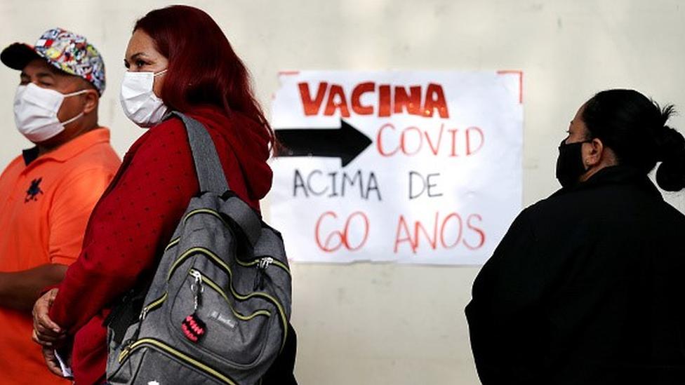 Pessoas de máscara em fila para vacinação. Ao fundo, placa escrito