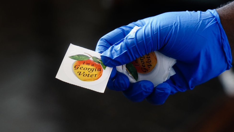 Voters are handed a sticker saying they voted