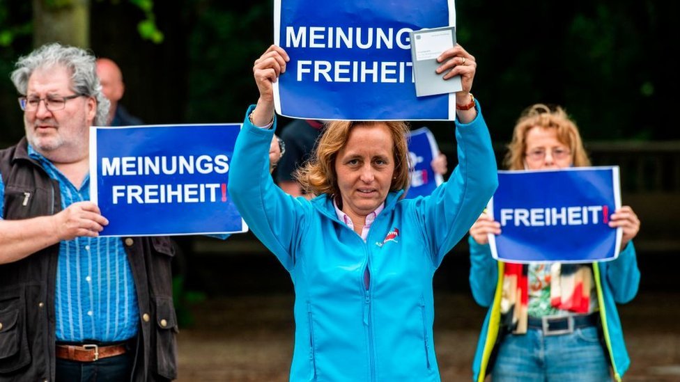 """Deputy Leader of the Alternative for Germany (AfD) Beatrix von Storch holds up a placard reading: """"Freedom of Speech"""" during a protest against lockdown measures due to the new coronavirus COVID-19 pandemic, in Berlin on May 23, 2020"""