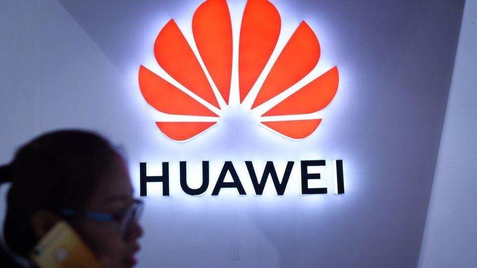 Mujer en frente del logo de Huawei.