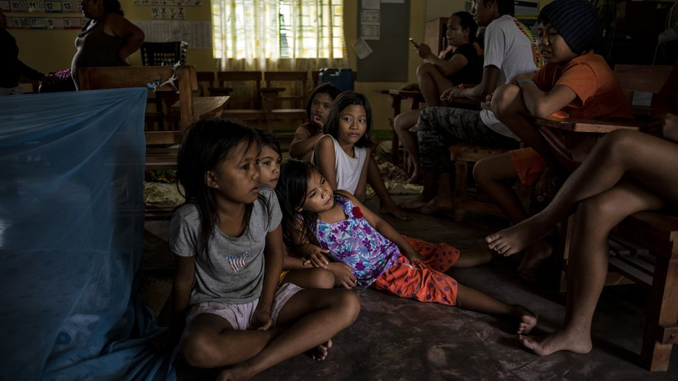 Children sitting on the floor of a classroom in Tuguegarao