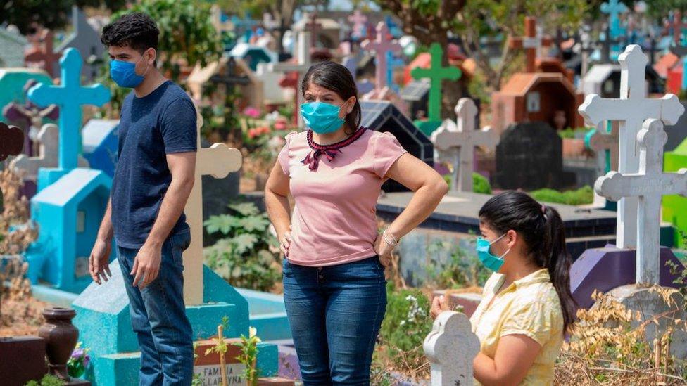 Deudos con mascarillas en un cementerio de Nicaragua