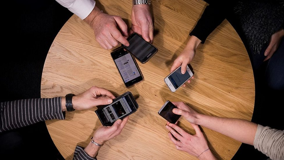 A group of people holding their mobile phones
