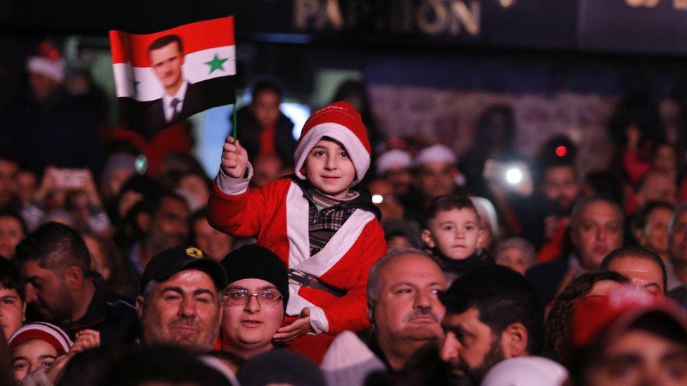 Dete maše zastavom sa Asadovom slikom na trgu u Damasku
