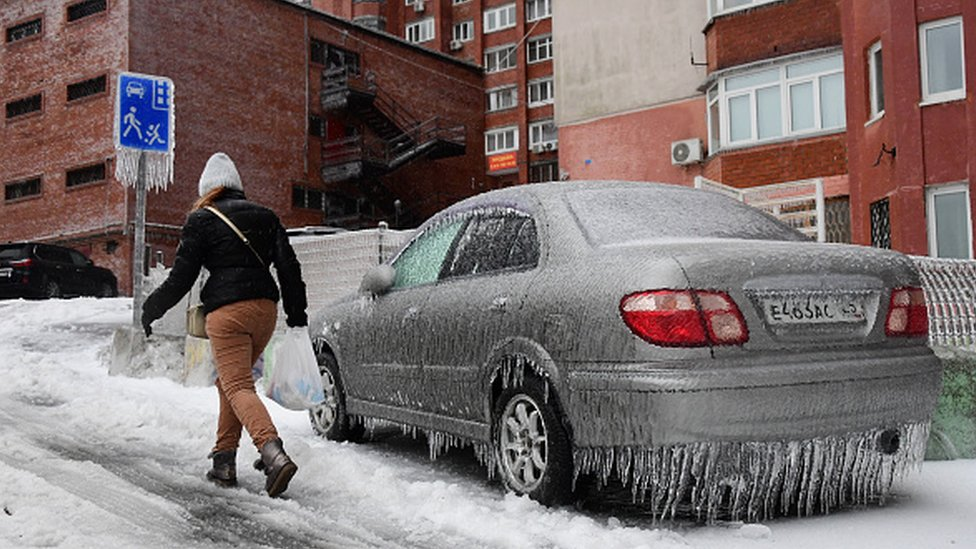A woman walks past a car covered with ice after a recent freezing rain in eastern Russia