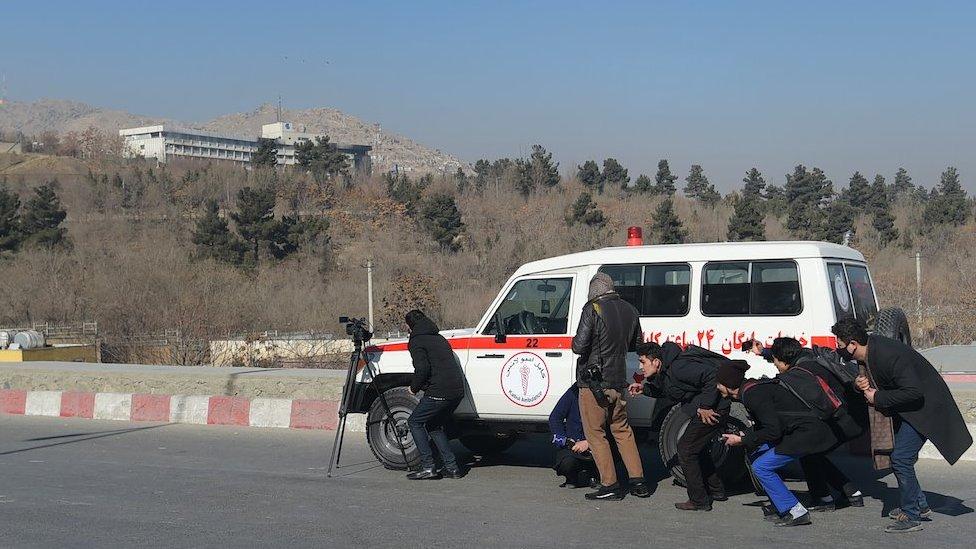 Periodistas escondidos detrás de un vehículo.