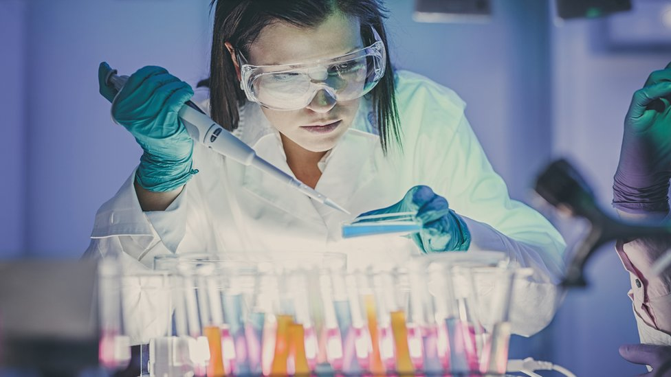 Woman scientist using pipette and test tubes
