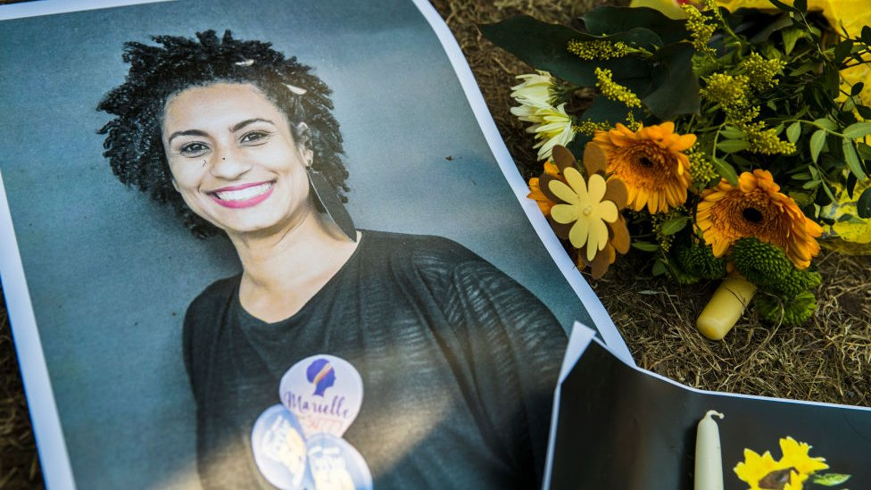 Fotografia de Marielle Franco ao lado de flores em sua homenagem