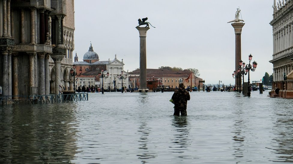 "A man stands in water at the flooded St Mark""s Square"
