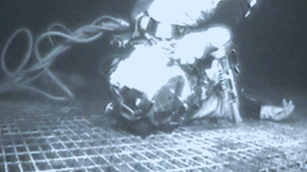 Chris Lemons deitado sobre estrutura no fundo do mar