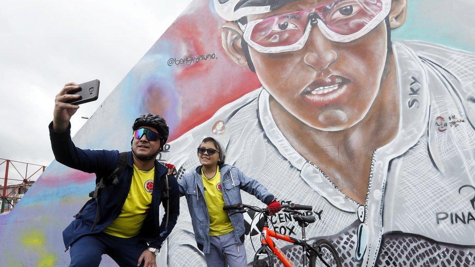 Dos aficionados se fotografía frente a un mural con el rostro de Egan Bernal en Zipaquirá.